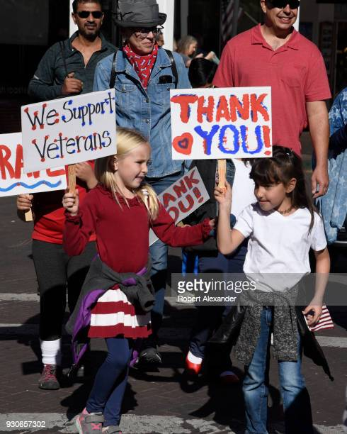 Children walking in a Veterans Day parade in Santa Fe New Mexico hold signs expressing their support and gratitude for America's military veterans