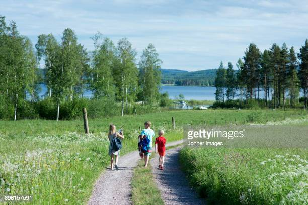 children walking in dirt road - レクサンド ストックフォトと画像