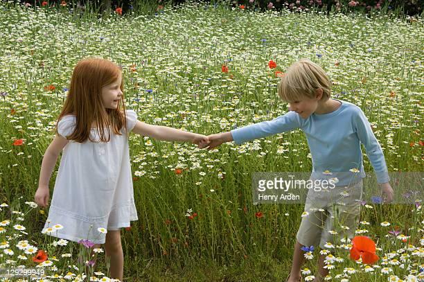 Children walking in field of flowers