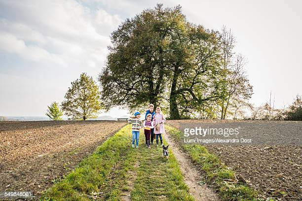 children walking on farm track - alexandra dost stock-fotos und bilder