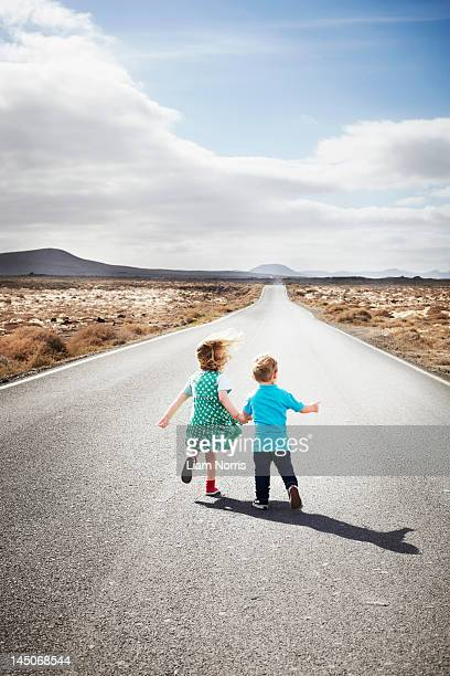 children walking on paved rural road - orphan stock pictures, royalty-free photos & images