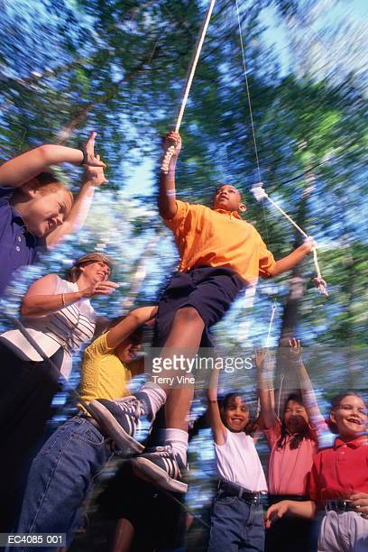 Children (6-8) walking on rope, teacher alongside, low angle view