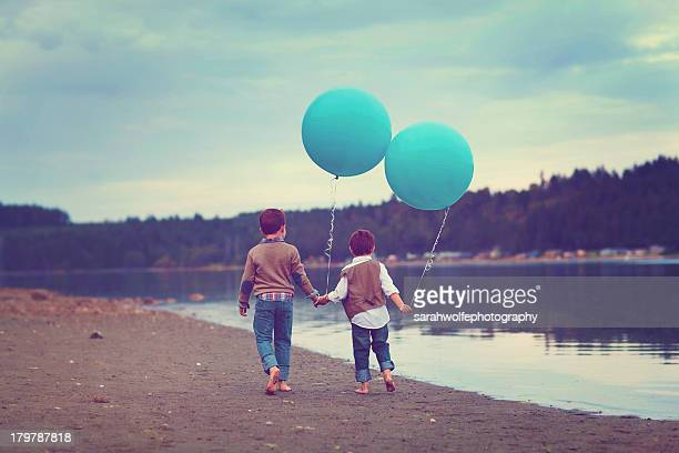 Children walking on the beach with blue balloons