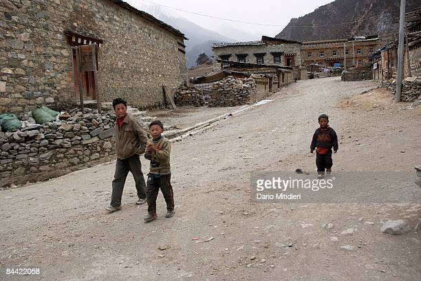 Children walking on the street of a little village in Yading a reserve in southwest Sichuan Province China This area of southwestern China is...