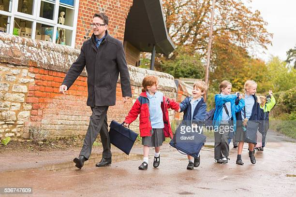 Children Walking Out of School With Their Teacher