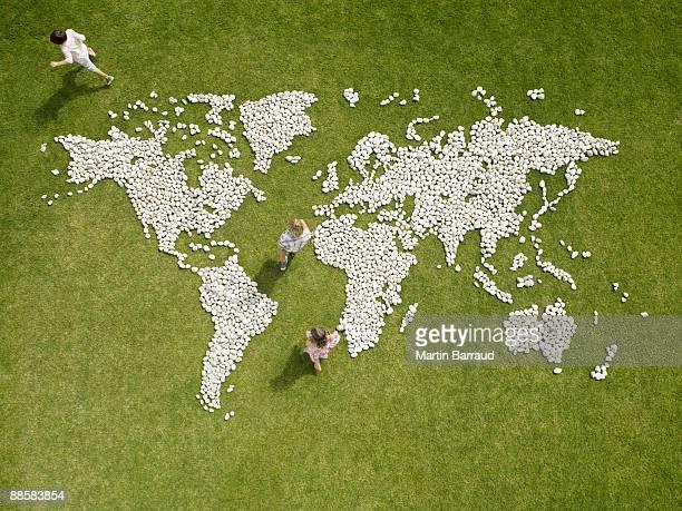 Children walking through world map made of rocks