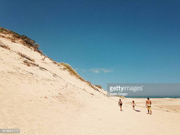Children walking towards sand dune with father