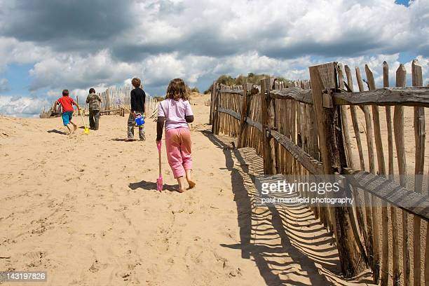 children walking up sand dune - camber sands stock photos and pictures