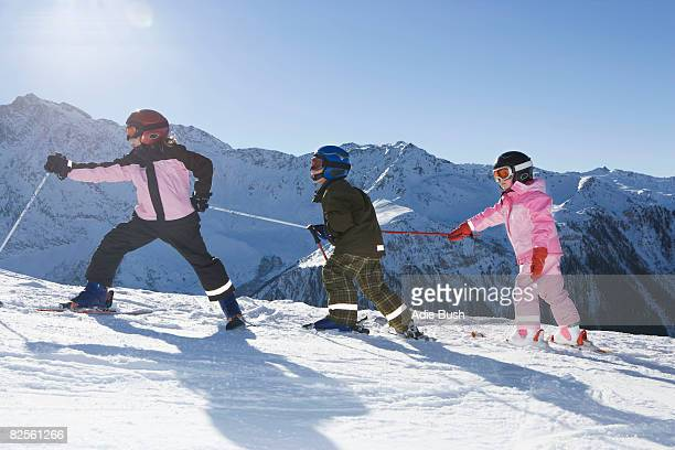 Children walking up slope with skis on