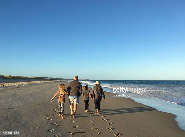 Children walking with grandparents at the beach
