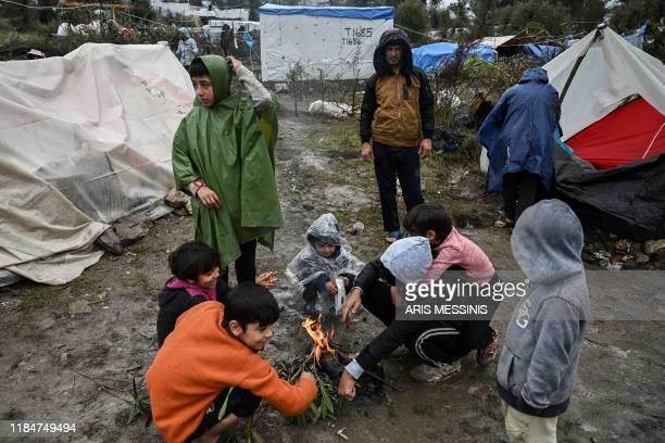 Children warm themselves around a camp fire under the rain in the refugee camp of Moria on the island of Lesbos on November 26 2019 Conditions remain...