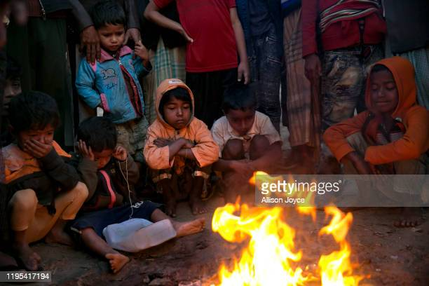 Children warm themselves by a fire in a Rohingya refugee camp on January 23, 2020 in Cox's Bazar, Bangladesh. On Thursday, the International Court of...