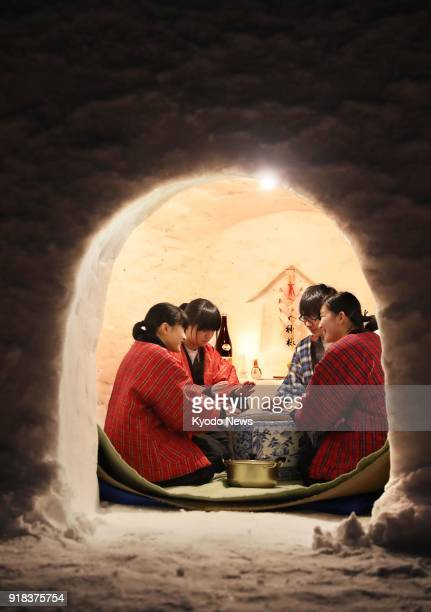 Children warm themselves with a charcoal brazier inside a snow hut in Yokote Akita Prefecture northeastern Japan on Feb 14 ahead of the Feb 1516...