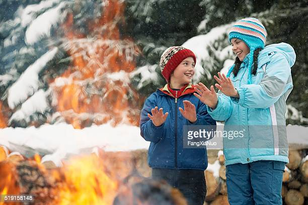Children warming hands by a fire