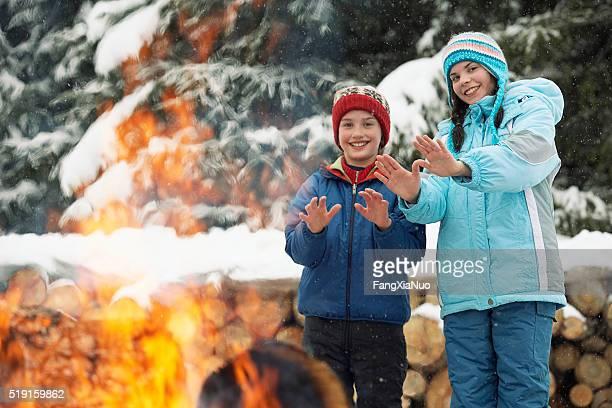 Children warming their hands by a fire