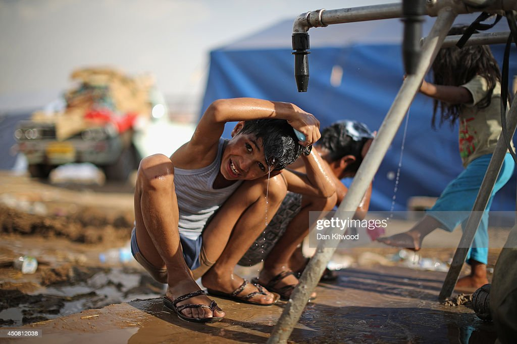 Children wash at a well at a temporary displacement camp on June 13, 2014 in Kalak, Iraq. Thousands of people have fled Iraq's second city of Mosul after it was overrun by ISAS (Islamic State of Iraq and Syria) militants. Many have been temporarily housed at various IDP (internally displaced persons) camps around the region including the area close to Erbil, as they hope to enter the safety of the nearby Kurdish region.