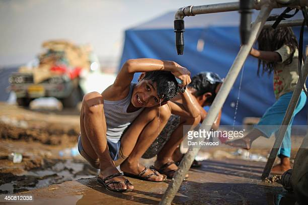 Children wash at a well at a temporary displacement camp on June 13, 2014 in Kalak, Iraq. Thousands of people have fled Iraq's second city of Mosul...
