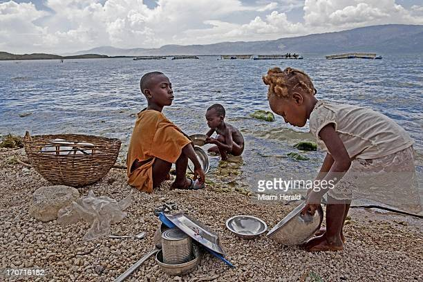Children wash dishes at the shore of the Madan Belize village on Lake Azuei near the Haitian/Domincan border The vast majority of the residents of...