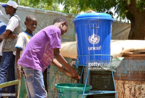Children wash their hands with a bucket bearing the lettering 'Unicef' in a camp for internally displaced people home to some 300000 Nigerian...