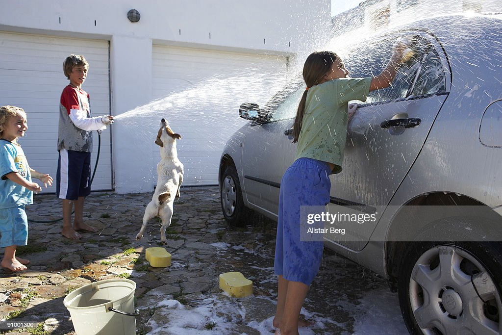 Children washing car with pet dog : Stock Photo
