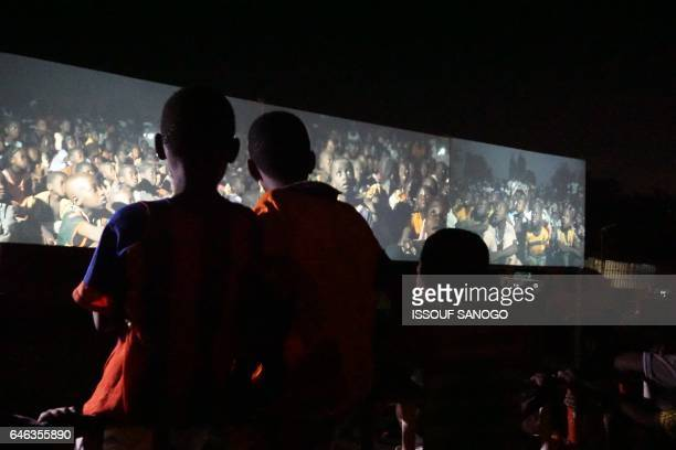 Children watch a documentary film during an open screening on the sidelines of the Pan-African Film and Television Festival in Ouagadougou on...