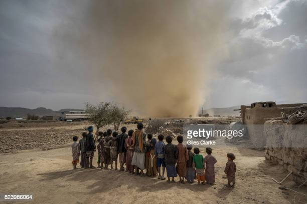 Children watch a mini tornado whip up sand as it travels across the desert landscape near the town of Huth situated about 80km north of Yemen's...