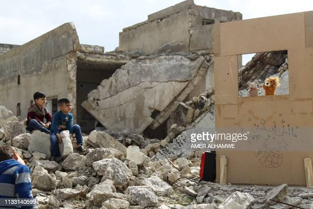 TOPSHOT Children watch a puppet show performed by a Syrian actor through a makeshift puppet theatre set up among the rubble of collapsed buildings in...