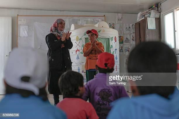 Children watch a puppet show to lear about hygiene at an Oxfam community centre in Zaatari refugee camp, Jordan, on September 7, 2015.