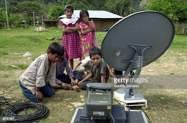 Children watch a television monitor February 22, 2001 in the tiny village of Ovintic, next to a satalite installed by a journalist to cover the 15...