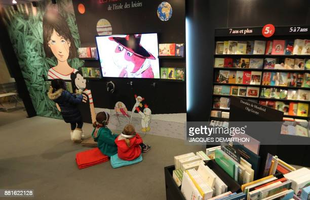 Children watch a video at the Salon du livre et de la presse jeunesse in Montreuil eastern Paris on November 29 2017 DEMARTHON