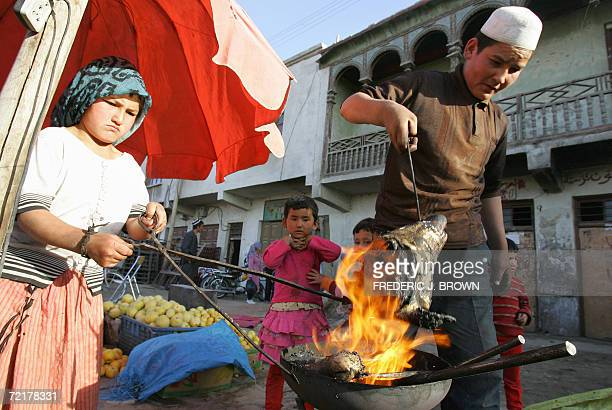 Children watch as a goat's head is held over a fire to burn off the hair before being scraped clean and boiled with intestines for a Uighur dish...