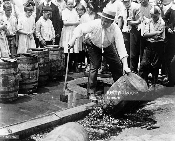 Children watch as a prohibitionist destroys a barrel of beer with an ax during Prohibition in the United States