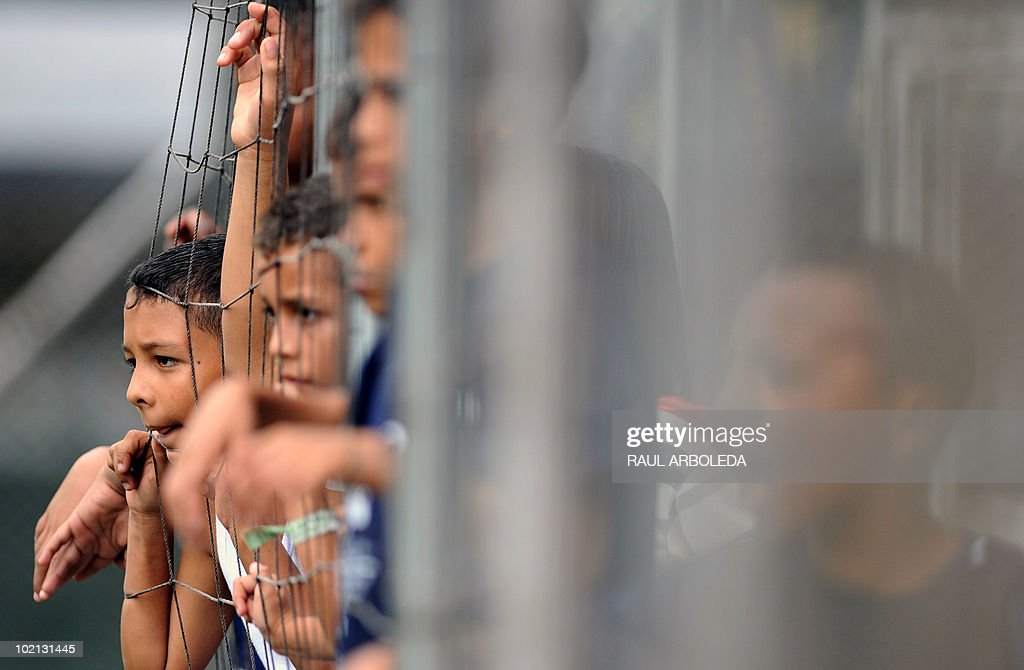 Children watch as others play during the 'Mundialito' football tournament in Medellin, Antioquia department, Colombia on June 15, 2010. The 'Mundialito' tournament takes place every four years with the participation of Medellin soccer schools. AFP PHOTO/Raul ARBOLEDA