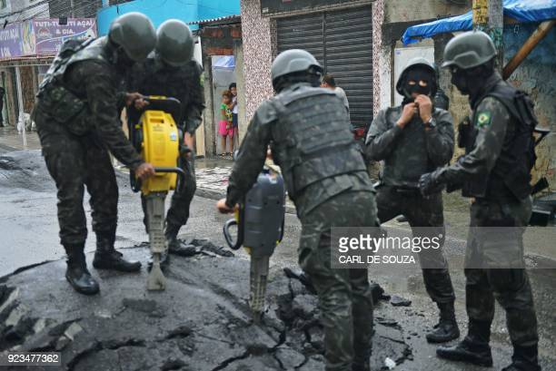 Children watch as soldiers remove a roadblock made by drug traffickers near the Vila Kennedy favela in Rio de Janeiro on February 23 2018 More than...