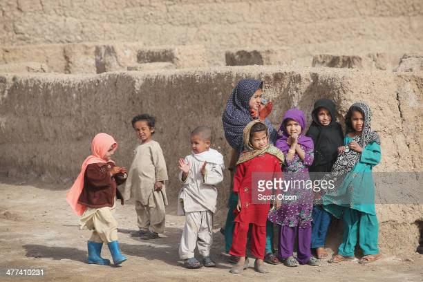 Children watch as soldiers with the US Army's 4th squadron 2d Cavalry Regiment patrol through their village on March 9 2014 near Kandahar Afghanistan...