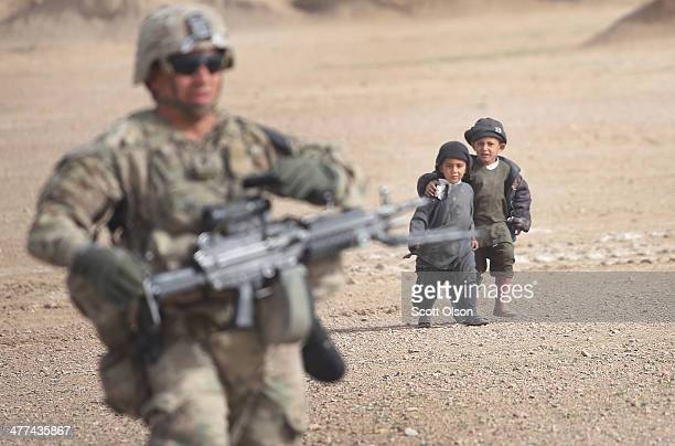 Children watch as SPC Wilmer Bolivar from Pembroke Pines Florida with the US Army's 4th squadron 2d Cavalry Regiment patrols through their village on...