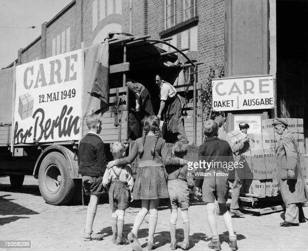 Children watch CARE parcels being unloaded at a warehouse in Berlin, immediately after the lifting of the Berlin blockade, 18th May 1949. CARE stands...