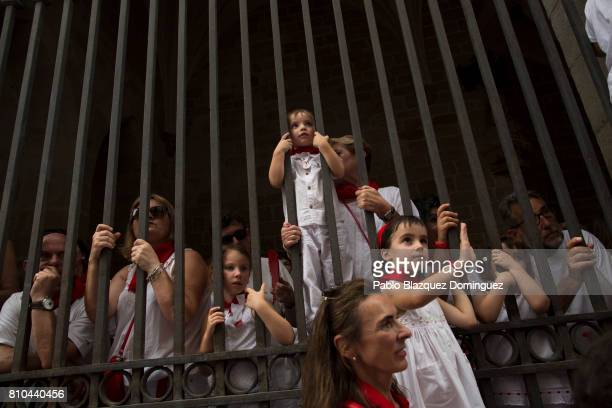 Children watch from behind a fence the Comparsa de Gigantes y Cabezudos or Giants and Big Heads parade on the second day of the San Fermin Running of...