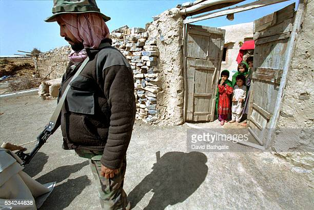 Children watch from the safety of their house compound, as U.S. Army and Afghan Military soldiers search the surrounds for weapons and intelligence.