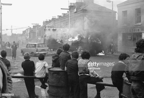 Children watch hijacked vehicles burn following rioting on the Lower Falls Road Belfast 17th September 1976