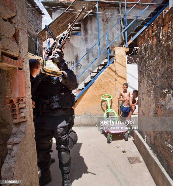 Children watch policemen at Morro do Alemao shantytown on November 29 2010 in Rio de Janeiro Brazil Police scoured the sewers under Rio's sprawling...