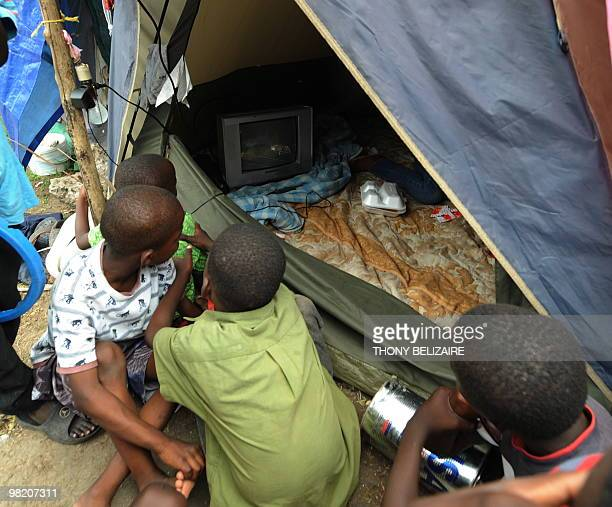 Children watch television on April 01 2010 in a tent city of PetionVille a neighborhood of PortauPrince The global community has pledged nearly 10...