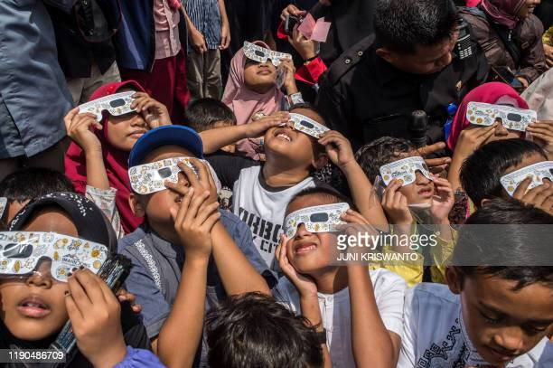 Children watch the moon move in front of the sun in a rare ring of fire solar eclipse in Surabaya on December 26 2019