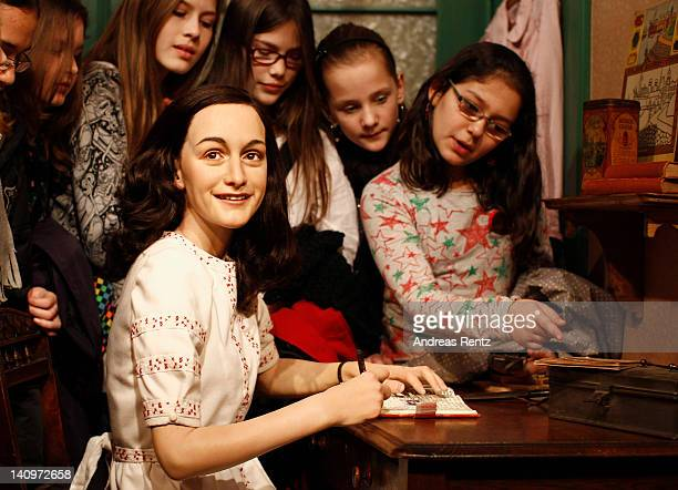 Children watch the wax figure of Anne Frank and their hideout reconstruction at Madame Tussauds on March 9 2012 in Berlin Germany