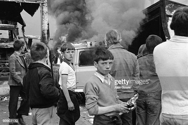 Children watch vehicles burn following rioting on the Lower Falls Road Belfast 17th September 1976