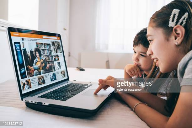 children watching a guitar video online lesson at home in isolation using laptop - remote location stock pictures, royalty-free photos & images