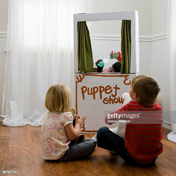children watching a puppet show - puppet show stock photos and pictures