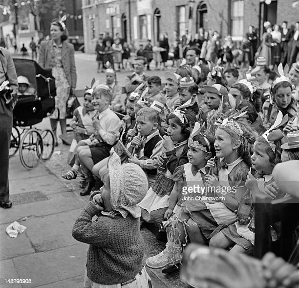 Children watching a show at a party to celebrate the coronation of Queen Elizabeth II held in Morpeth Street in London's East End 2nd June 1953...