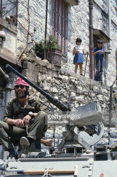 Children watching a soldier sitting next to the gun turret on an armoured vehicle in Beirut 1970s