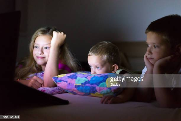 就寝前にノートに漫画を見ている子供